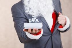 Santa Claus holding a gift box with ribbon