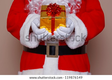 Santa Claus holding a gift wrapped present with gold wrapping paper and a red bow and ribbon.