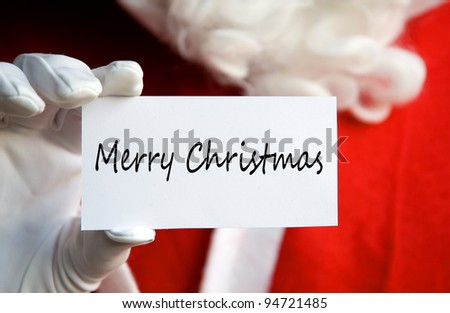 Santa Claus holding a Merry Christmas card in a white gloved hand