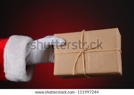 Santa Claus holding a parcel tied with twine over a light to dark red background. Horizontal format showing hand and arm only.