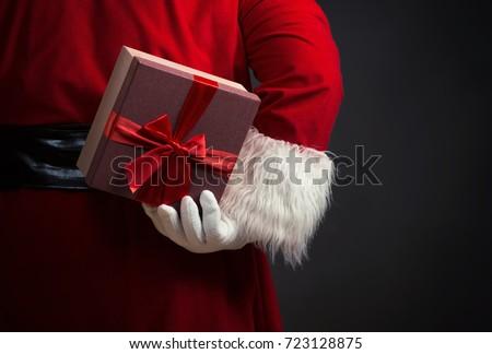 Santa Claus holding a present behind his back, close up #723128875