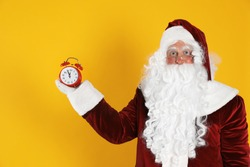 Santa Claus holding alarm clock on yellow background. Christmas countdown