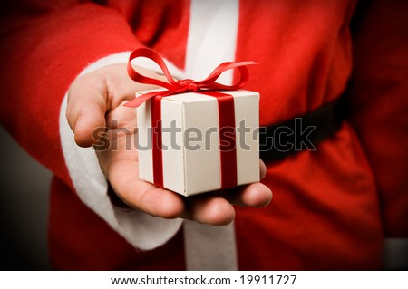 Santa Claus holding and offering a gift on his hand.