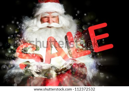 Santa Claus holding his bag and smiling. Lights and sparks are flying from the bag. Sale sign in front of Santa