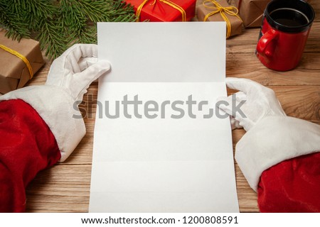 Santa Claus holding letter on wooden table with gift boxes and Christmas tree and cup of hot coffee or tea.  mockup blank #1200808591