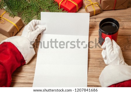 Santa Claus holding letter on wooden table with gift boxes and Christmas tree and cup of hot coffee or tea.  mockup blank #1207841686