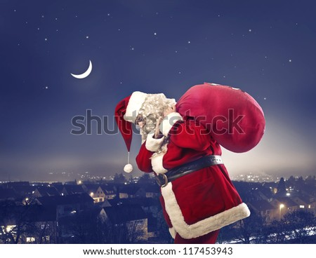 Santa Claus holding the bag with the presents on a town background