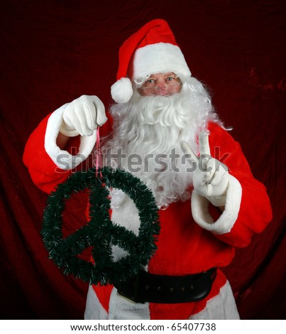 Santa Claus holds a Christmas Peace Sign Wreath and flashes a Peace Sign with his left hand