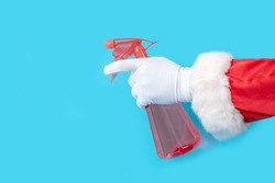 Santa Claus holds red dispenser on the blue background. Hands of Santa with sprayer for cleaning.