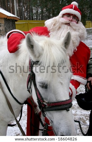 Santa Claus holds white horse