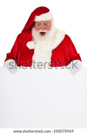 Santa Claus in authentic look behind blank sign with surprised expression. All on white background.