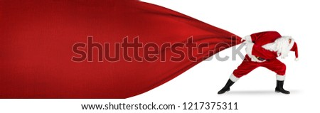 Santa claus in hopeless fight to pull huge big red gift bag with copy space texture isolated on white background #1217375311