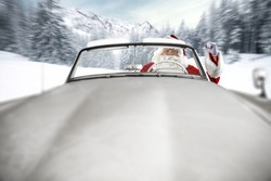 Santa Claus is riding a white cabriolet. Big white retro car. Winter road between trees and mountains.
