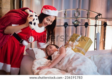 santa claus lady give gifts to children who were sleeping on the bed in Christmas day