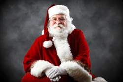 Santa Claus looking into the camera with traditional background and hands crossed in front of him