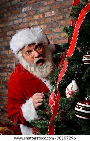 Santa Claus looking surprised as he is sneaking around the Christmas Tree.
