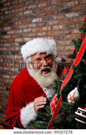 Santa Claus looking surprised as he is sneaking around the Christmas Tree with copy space above him.