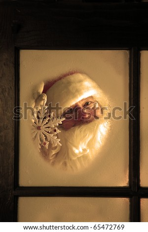 Santa Claus looks out through the snow and fog on his workshop window in the north pole to see outside check the weather while he holds up a large snow flake on December 24th, Christmas Eve - stock photo