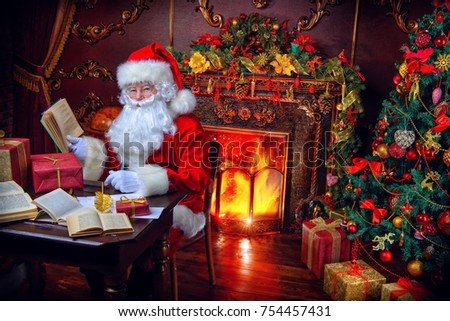 Santa Claus makes a list of gifts, sitting at home by the fireplace and Christmas tree. Christmas scene. The time of miracles.