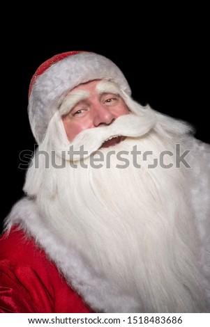 Santa Claus on a black background. The majestic and fabulous portrait of Santa Claus on a black background, who carefully and cunningly looks, smiles and laughs cheerfully and laughs. #1518483686