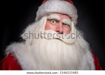 Santa Claus on a black background. The majestic and fabulous portrait of Santa Claus on a black background, who carefully and cunningly looks, smiles and laughs cheerfully and laughs. #1546515485