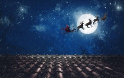 Santa Claus on his sleigh, pulled by reindeer, flying at night to deliver gifts