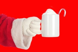 Santa Claus on red background. Santa Claus enjoys a mug of Hot Coco with whip cream and a Candy Cane with a Christmas Red background. Merry Christmas to all.