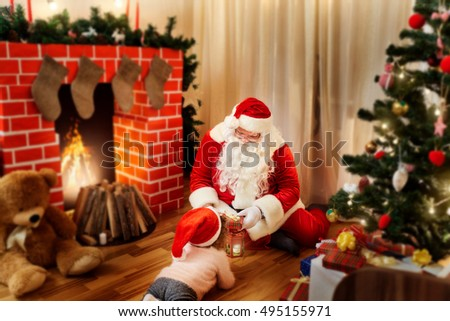 Santa Claus on the floor in the house gives gifts to the child in a hat for Christmas, a happy New Year.