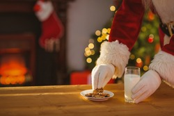 Santa claus picking cookie and glass of milk on the table at home