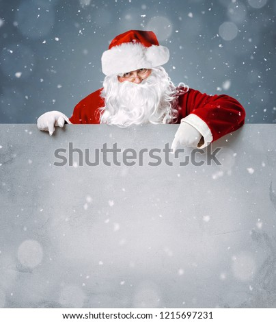 Santa Claus pointing in blank advertisement banner with copy space