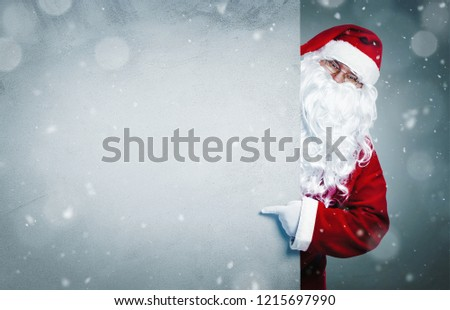 Santa Claus pointing on blank advertisement banner with copy space  - Shutterstock ID 1215697990