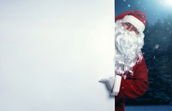 Santa Claus pointing on blank white wall, advertisement banner with copy space