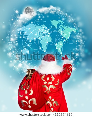 Santa Claus preparing for Christmas. He is looking at digital worldmap to see children list to greet with gifts. Modern technologies in traditional events concept