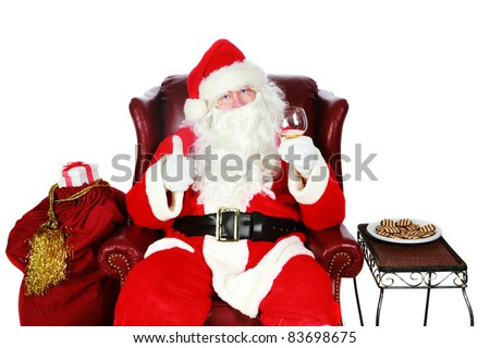 "Santa Claus raises a toast of ""Good Cheer"" to You the Viewer while on his easy chair one fine Christmas Evening. Isolated on white with room for your text"