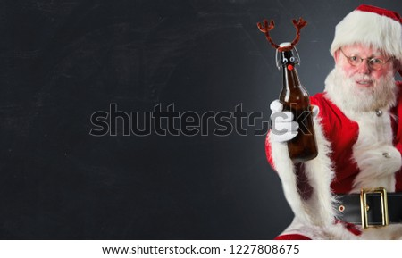 Santa Claus raising a Christmas toast with a bottle of beer decorated with deer antlers over grey with copy space