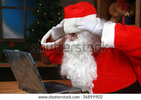 Santa Claus reacts to his e-mail on his laptop computer