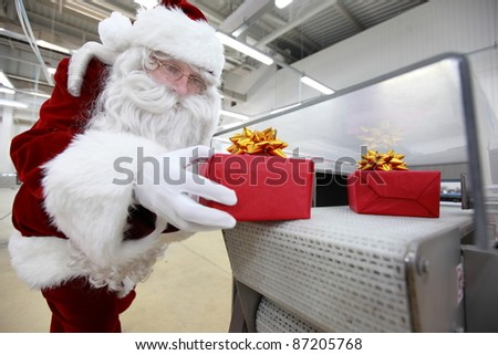 santa claus receiving gifts from presents production line in factory