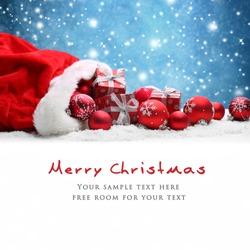 Santa Claus red bag with Christmas balls and gift box on snow.