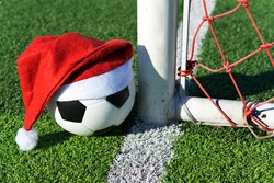 Santa Claus red hat on soccer ball at green grass