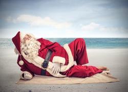 Santa Claus relaxes lying on the beach