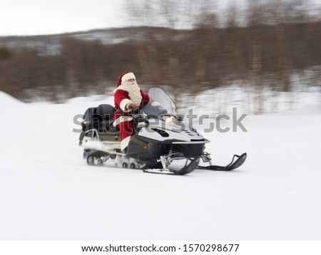 Santa Claus riding a Skidoo through the snow