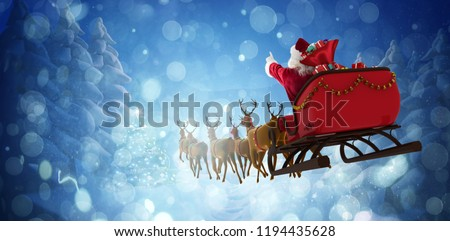 Santa Claus riding on sleigh with gift box against winter village