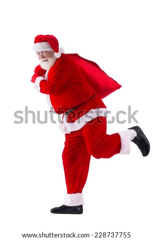 Santa Claus running to deliver Christmas gifts - Shutterstock ID 228737755