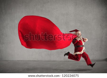 Santa Claus running with a very big sack full of presents - stock photo