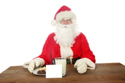 Santa Claus. Santa Claus aka Chris Kringle enjoys Cookies and Milk left for him one Christmas Eve. Isolated on white. Room for text.