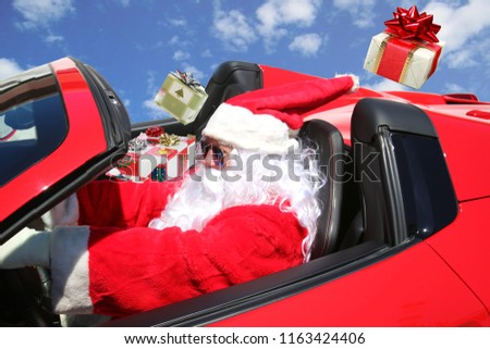 Santa Claus. Santa Claus Delivers Xmas Gifts while driving Fast in his Red Hot Rod Sports Car. Blue Sky background.