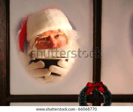 Santa Claus seen through a frosted window holding a large mug of cocoa. Horizontal format.