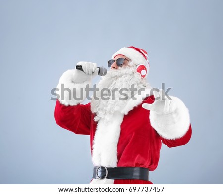Santa Claus singing Christmas songs on light background #697737457