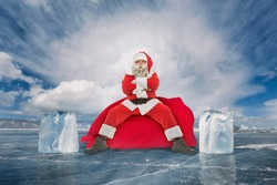 Santa Claus sits on a bag with gifts in the middle of a frozen winter lake