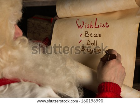 Santa Claus sitting at home and writing on old paper roll to do list with feather pen and ink at night with candle light. Authentic vintage style portrait.